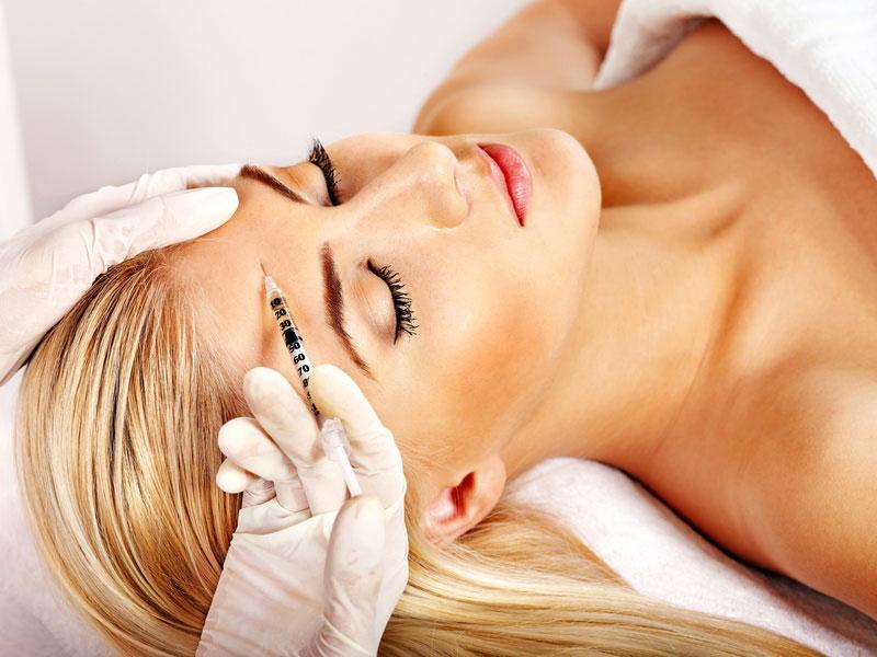 Botox-Injektion am Kopf einer Frau